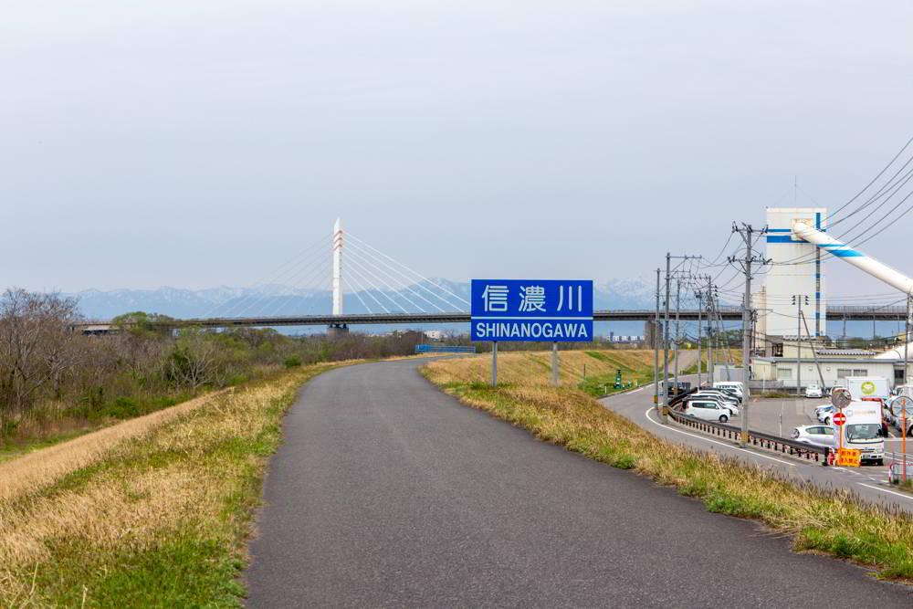 Tour am Shinano-Fluss in Niigata: Weg auf dem Deich und Brücke, Berge im Hintergrund