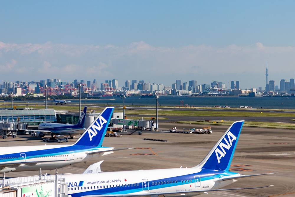 Los geht die Reise am Terminal 2 am Flughafen Haneda in Tokyo: ANA Flugzeuge am Terminal mit der Skyline Tokyos und dem Sky-Tree im Hintergrund.