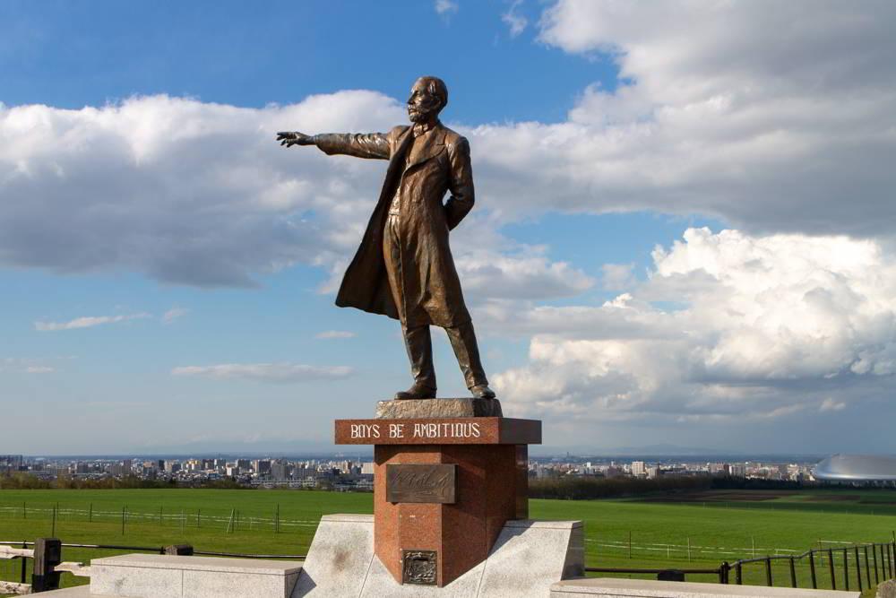 Die Statue von William S. Clarke, im Hintergrund Sapporo in der Ferne vor grünen Wiesen