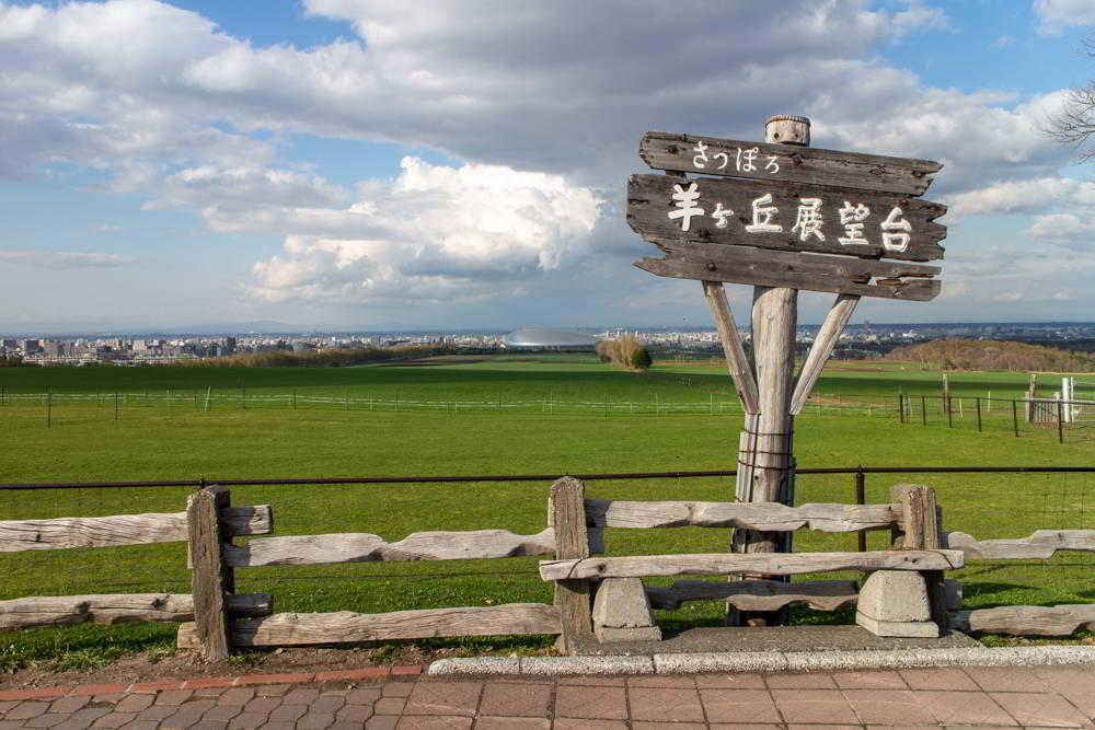 Hitsujigaoka Aussichtsplattform - ein Schild vor grüner Wiese und Sapporo in der Ferne