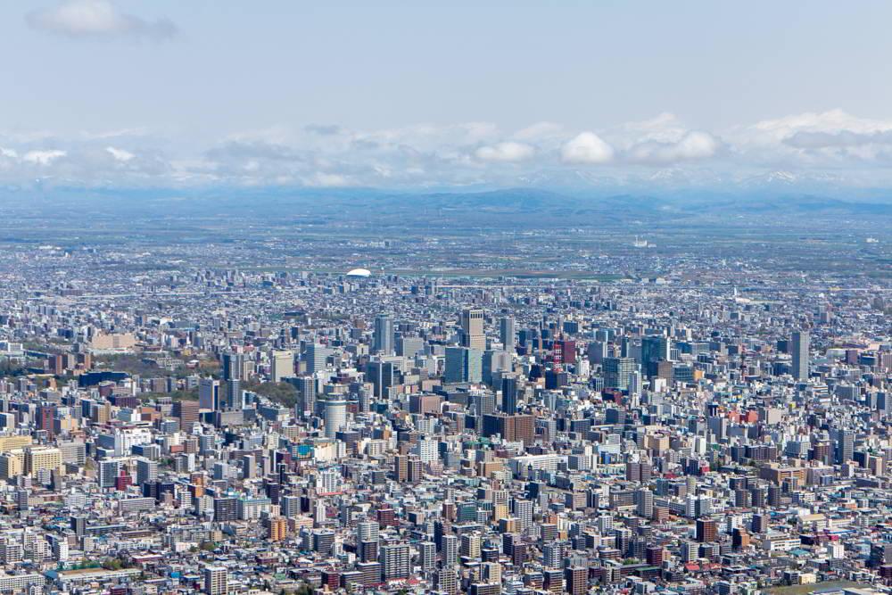 Blick vom Berg Moiwa über Sapporo mit dem Meer im Hintergrund und der Skyline vorne.