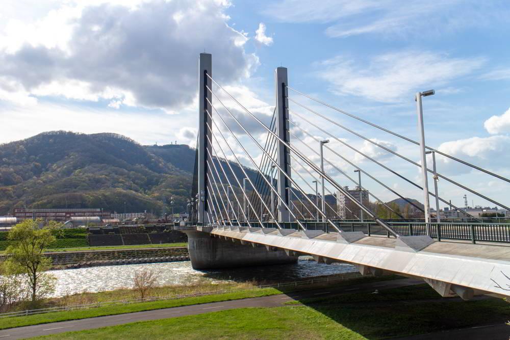 Blick auf die München-Brücke in Sapporo mit Bergen im Hintergrund.