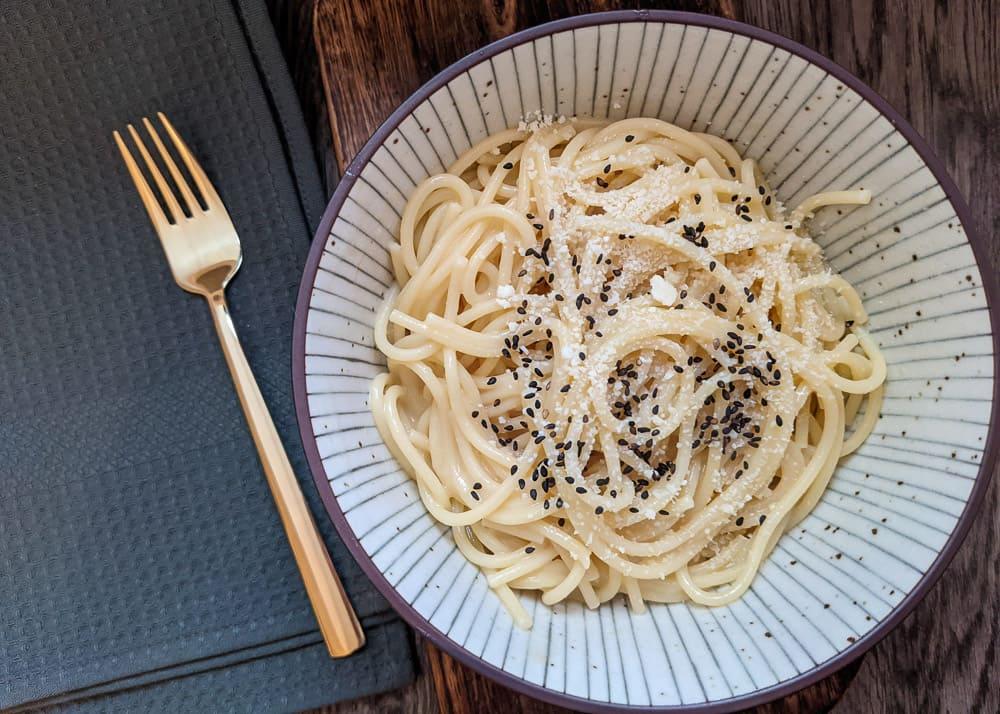 Schüssel mit Spaghetti in einer Bütter-Miso-Soße. Darüber etwas Parmesan und schwarzer Sesam